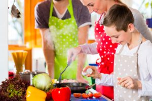 Family cooking healthy food in domestic kitchen