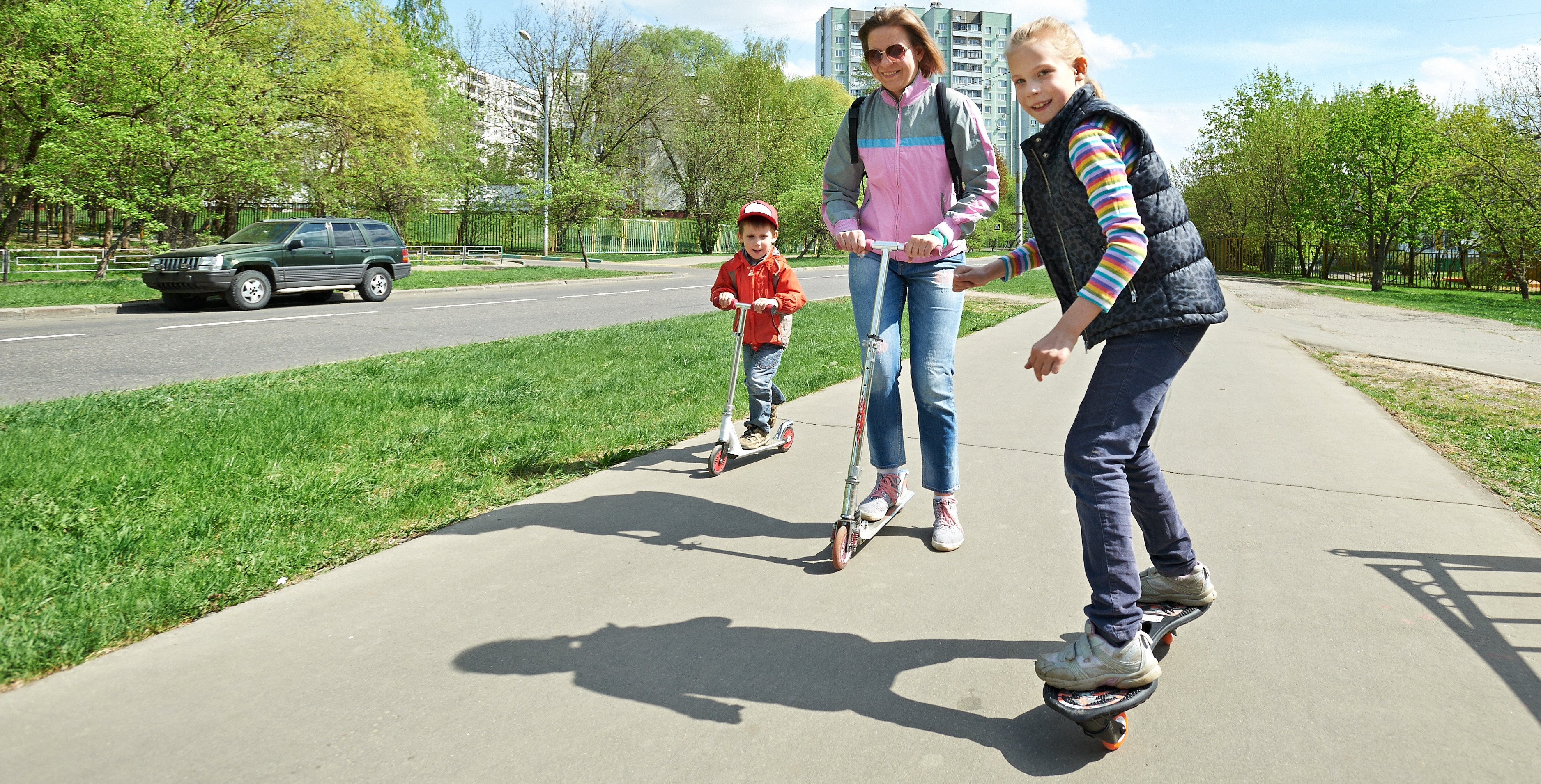 Family riding a skateboard and scooter in town