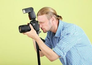 Handsome photographer with camera on monopod, on green backgroun