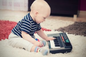 Little baby boy plays on keyboard toy. baby piano music playing child white cute little concept
