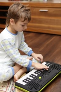 Boy playing on a synthesizer at home