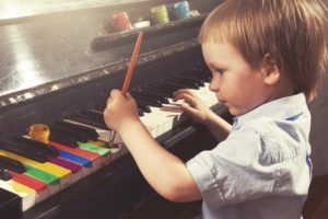 Young boy painting piano keys with brush. True art