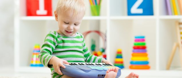 Happy little kid toddler boy having fun playing piano toy sitting on floor in nursery. Kinderkeyboard-Test