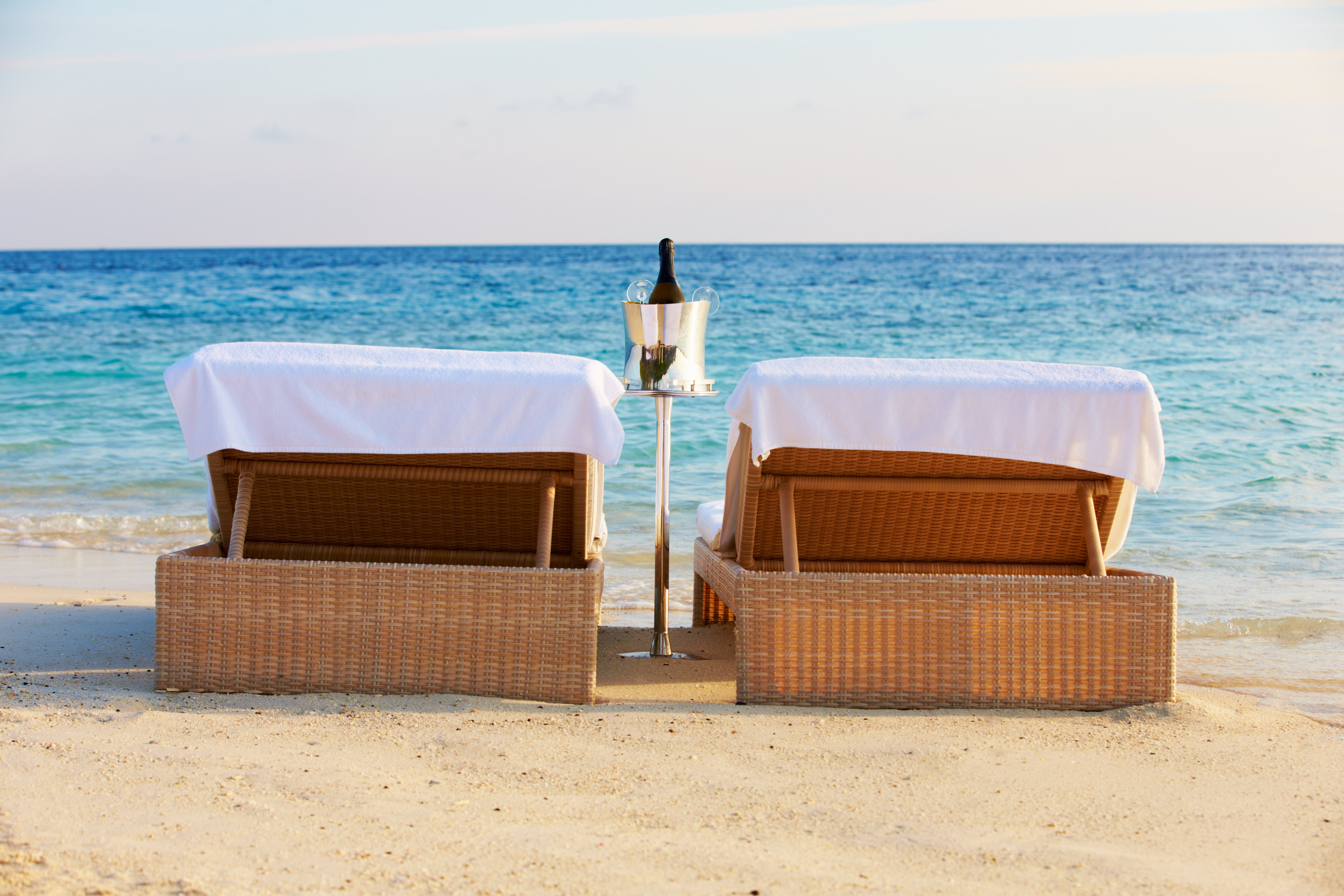 Loungers At Edge Of Tropical Sea With Champagne Bucket